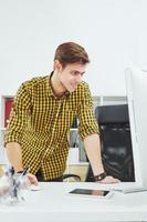 den unga mannen bakom skrivbordet på kontoret foto