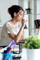 ganska ung kvinna som använder sin bärbara dator på kontoret. foto