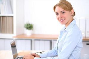 ung blond affärskvinna med bärbar dator på kontoret foto