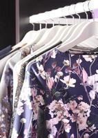 kvinnlig klädsamling på galgar i modebutik foto