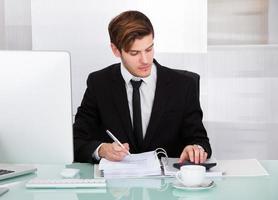 affärsman som använder miniräknare foto
