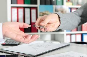 fastighetsmäklare som lämnar nycklarna till sin klient
