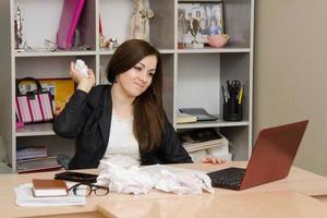 tjej kommer att kasta skrynkligt papper i datorskärmen foto