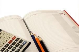 anteckningsblock, miniräknare tre blyertspennor foto