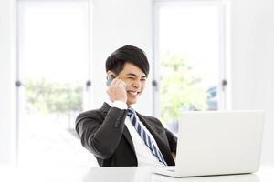 ung affärsman prata lyckligt med smart telefon i office foto