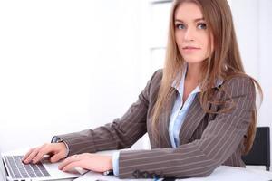 ung affärskvinna som sitter vid skrivbordet på kontorsbakgrund foto