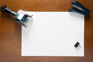 stämpel och tomt pappersark på ett kontorsskrivbord foto