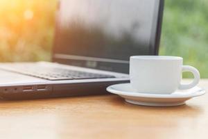 kopp kaffe och bärbar dator på bordet foto