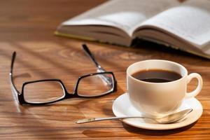 kopp kaffe, bok och glasögon foto