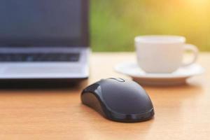 närbild mus med bärbar dator och kaffe på bordet foto