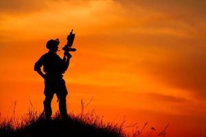 silhuett av militär soldat eller officer med vapen vid solnedgången foto