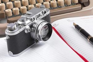 gammal skrivmaskin, gammal reservoarpenna och fotokamera foto
