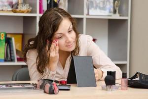 tjej lägger grund på ansiktet på jobbet foto