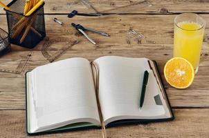 tomt anteckningsblock med ett glas färsk apelsinjuice foto