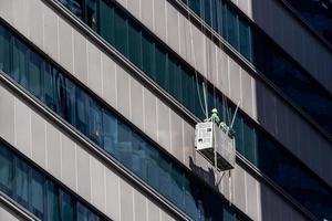 höghusfönster städare i singapore som arbetar på skyskrapa foto