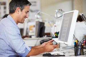 en man som använder sin mobiltelefon på sitt skrivbord på kontoret foto