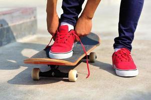 kvinna skateboarder knyta skosnören