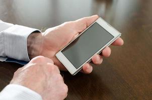 man håller sin smartphone