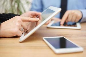 affärsman och affärskvinna använder surfplatta på kontorsskrivbord foto