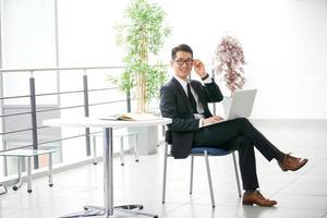 ung asiatisk affärsman som använder surfplatta, mobiltelefon på kontoret foto