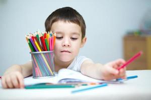 liten pojke håller färgpennor foto