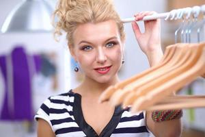 vacker ung stylist kvinna nära rack med hängare foto