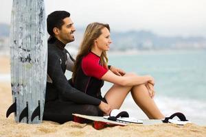 unga par som vilar på stranden foto