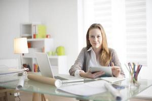 vacker ung kvinna på arbetsplatsen med en digital surfplatta foto