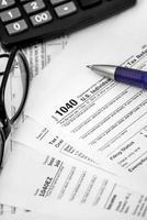oss skatteformulär 1040 med penna, glasögon och miniräknare foto