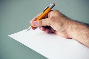 närbild av handen med penna och papper foto