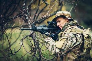 soldat med gevär i skogen