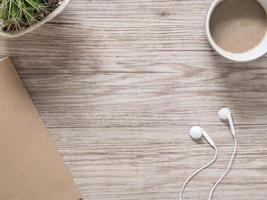 hörlurar, anteckningsbok och kaffe på träbakgrund foto