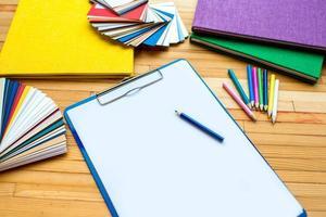 vitt pappersark med färgglada prover och böcker foto