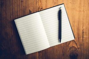 öppen anteckningsbok med tomma sidor och penna foto