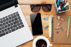 arbetsplats med laptop kaffetelefon och anteckningsbok foto