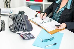 affärskvinna noterar en tid i sin dagbok