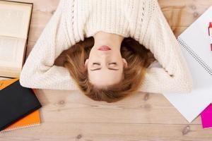 avslappnad ung studentkvinna som ligger på golvet foto