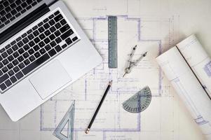 en bärbar dator öppen med ritningar och arkitektoniska verktyg foto