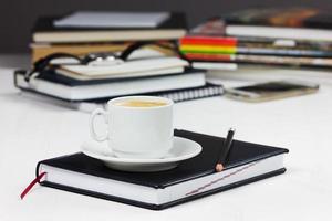 arbetsplats med affärsdagbok, penna, kaffe, klocka och mobiltelefon foto