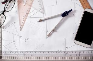 arkitekten skrivbord med papper, linjal, kompasser och mobiltelefon foto
