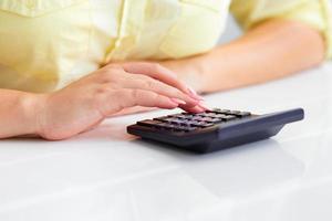 kvinnans händer med en miniräknare foto