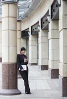asiatisk affärskvinna som står utanför i modern stad. foto