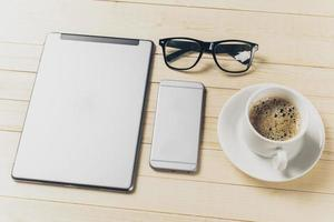 mobiltelefon och surfplatta med anteckningsbok på skrivbordet foto