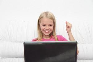 liten flicka med sin bärbara dator hemma foto