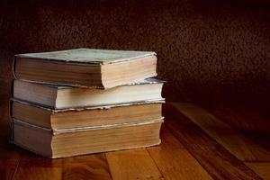 hög med gamla böcker på ett vackert träbord
