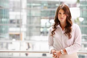 porträtt av en allvarlig ung affärskvinna, midjan upp foto