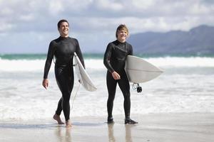 tonårssurfarar som bär ombord på stranden foto