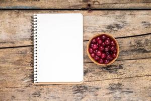 färska vilda bär med papper anteckningsbok på träbord. foto