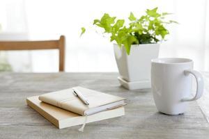 två böcker med penna och en mugg bredvid en växt på ett bord foto
