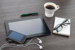 surfplatta, hörlurar, anteckningsbok och smart telefon med kaffe foto
